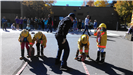 Firefighter Steven Wantuck advises fifth-graders in the fine art of rolling hose