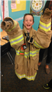 Young boy wearing large firemans coat