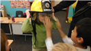 Boy putting visor down on Fire Rescue helmet another child is wearing