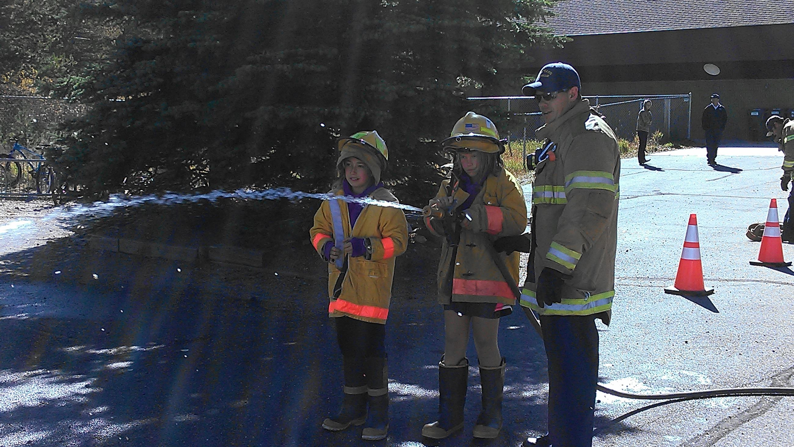 Fireman helping kids aim firehose