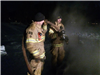 Two firemen with a hose